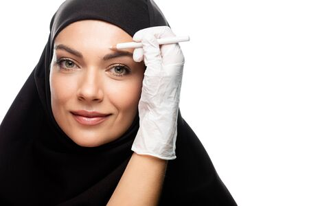 plastic surgeon marking young Muslim woman face for plastic surgery isolated on white