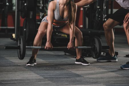 cropped view of trainer supporting sportswoman lifting barbell