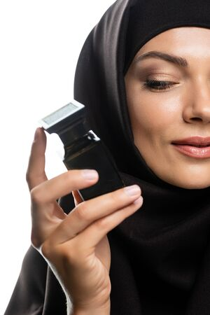 partial view of young Muslim woman in hijab holding bottle of perfume isolated on white