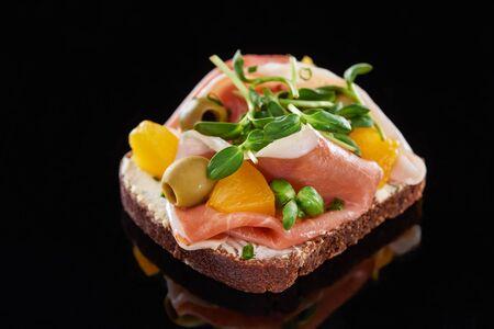 Selektiver Fokus von Schinken und Oliven auf gekochtem dänischem Smorrebrod-Sandwich auf Schwarz