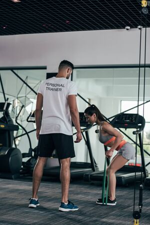 back view of personal trainer looking at athletic sportswoman exercising with resistance bands