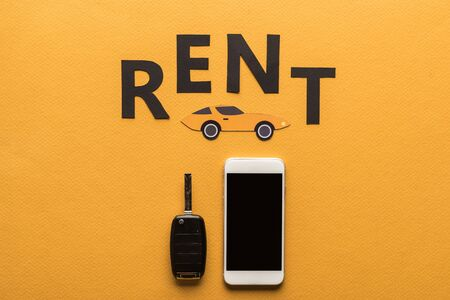 top view of smartphone with blank screen, car key, paper cut auto and black rent lettering on orange background Archivio Fotografico
