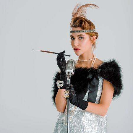 stylish woman with cigarette holder near retro microphone isolated on grey Reklamní fotografie