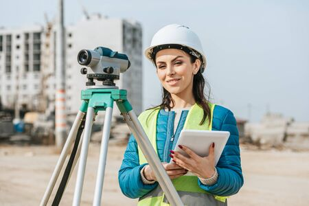 Surveyor with digital tablet and measuring level smiling at camera