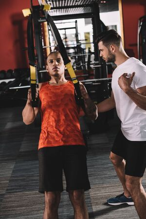 attentive trainer supporting young african american athlete pulling up on suspension trainer Stock Photo