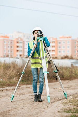 Female Surveyor measuring land with digital level Standard-Bild
