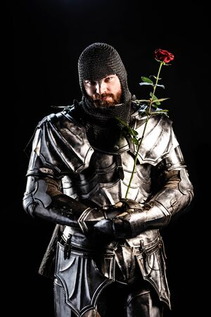 handsome knight in armor holding rose isolated on black Фото со стока