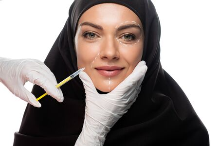 smiling young Muslim woman in hijab with marks on face having beauty injection isolated on white Stock fotó
