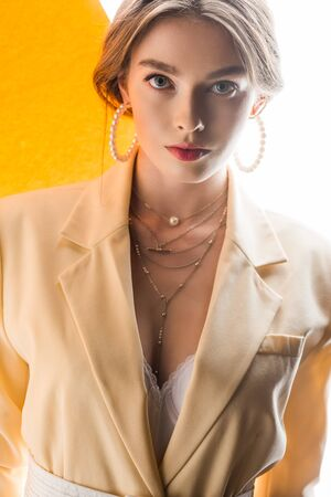 bella giovane donna in collana e orecchini che guarda l'obbiettivo su arancione e bianco