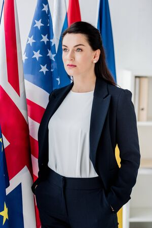 beautiful diplomat standing with hands in pockets near flags