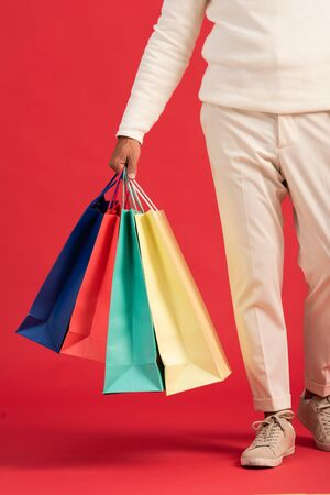 cropped view of man holding colorful shopping bags isolated on red