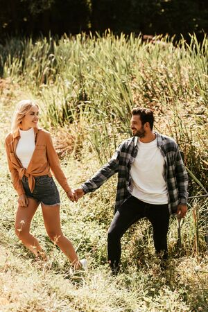 happy young couple holding hands while walking in thicket of sedge