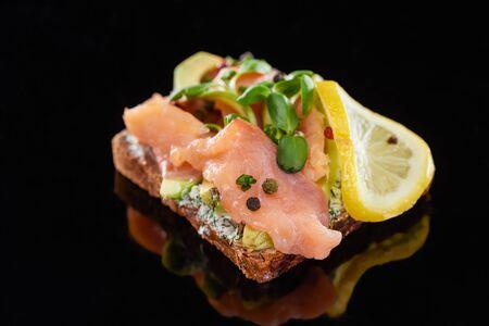 close up of lemon near salmon on danish smorrebrod sandwich on black 版權商用圖片