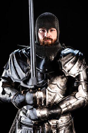 Schöner Ritter in Rüstung, der in die Kamera schaut und das Schwert isoliert auf Schwarz hält