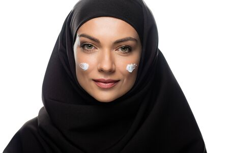 young Muslim woman in hijab with cosmetic cream on chicks isolated on white