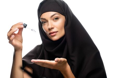 young Muslim woman in hijab holding dropper with serum isolated on white