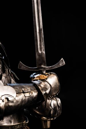cropped view of knight in armor holding sword isolated on black