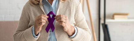 panoramic shot of retired woman holding purple ribbon at home