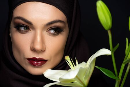 attractive Muslim woman in hijab with red lips near lily isolated on black Stock fotó