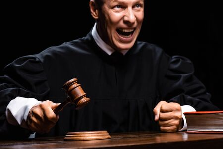 angry judge in judicial robe sitting at table and hitting with gavel isolated on black