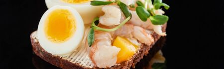 panoramic shot of rye bread with delicious shrimps on smorrebrod sandwich on black Stock Photo