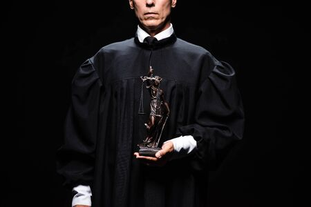 cropped view of judge in judicial robe holding themis figure isolated on black 版權商用圖片