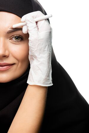 cropped view of plastic surgeon marking young Muslim woman face for plastic surgery isolated on white