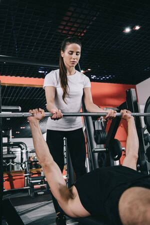 attentive, young trainer assisting sportsman lifting barbell in gym Stock Photo