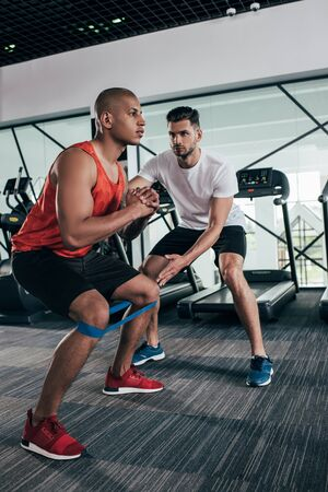 attentive trainer supporting african american sportsman warming up in gym