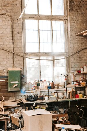 dusty workshop with brick walls and bottles on table Imagens