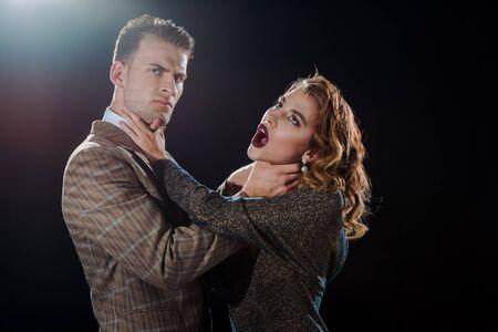 dangerous man choking attractive woman on black Stock Photo