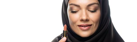 young Muslim woman in hijab holding beige lipstick isolated on white, panoramic shot