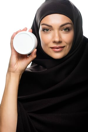 smiling young Muslim woman in hijab holding container with cosmetic cream isolated on white Stock fotó