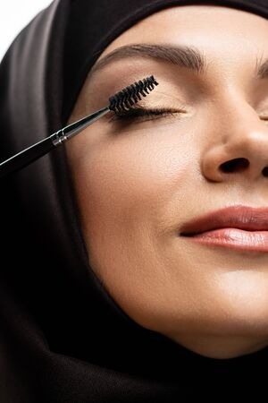 close up view of young Muslim woman in hijab applying mascara on eyelashes with closed eyes isolated on white