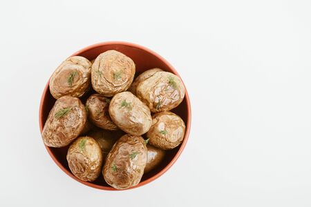 top view of delicious jacket potato with dill in clay bowl isolated on white Stock Photo