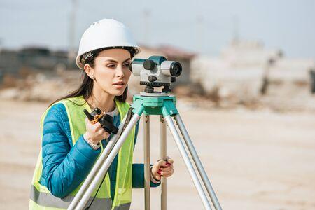 Topógrafo femenino con radio mirando a través del nivel digital Foto de archivo