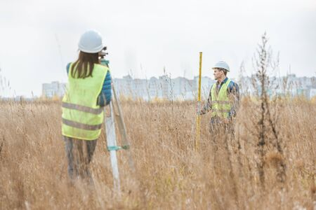 Surveyors working with digital level and ruler in field