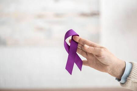 cropped view of woman holding purple ribbon at home