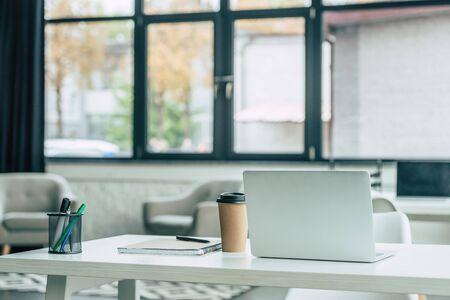 Laptop, Einwegbecher, Notizbuch und Stifthalter auf weißem Tisch im modernen Büro