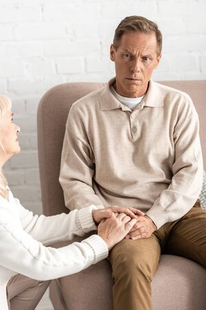 sad retired woman touching hands husband with mental illness