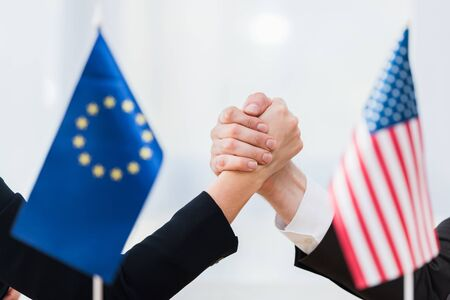 selective focus of diplomats holding hands near flags of usa and european union