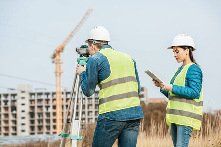Surveyors working with digital level and tablet in field Foto de archivo