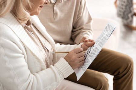 cropped view of senior man sitting with wife solving crossword