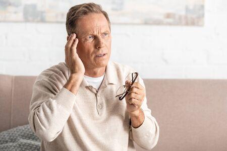 uomo anziano premuroso con perdita di memoria che tocca la tempia mentre tiene gli occhiali
