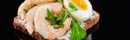 panoramic shot of boiled egg near shrimps on delicious danish smorrebrod sandwich on black Stock Photo