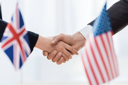 selective focus of diplomats shaking hands near flags of usa and united kingdom