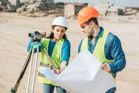 Surveyor with digital level pointing on blueprint to colleague Stock fotó