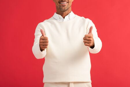 cropped view of cheerful man showing thumbs up isolated on red