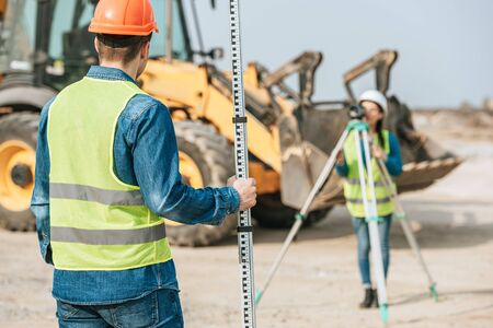 Selective focus of surveyors using ruler and digital level with bulldozer at background