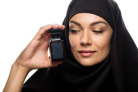 young Muslim woman in hijab looking at bottle of perfume isolated on white